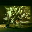 Still from Cairn Two: the actor is rising from the pile of bones.