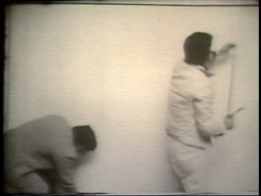 Still from Sequence 15 of Idea Demonstrations. Peter Kennedy and Mike Parr mark the periphery of the camera image.
