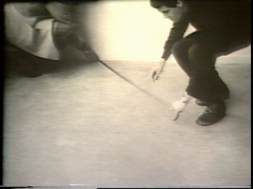 Still from Sequence 16 of Idea Demonstrations. Peter Kennedy and Mike Parr mark a perspictival line from the top left corner of the camera image.