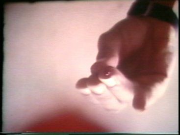 Still from Sequence 24 of Idea Demonstrations. Mike Parr drips blood onto the camera lens.