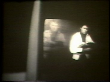 Still from Sequence 7 of Idea Demonstrations. Peter Kennedy moves in and out of his after image on the video screen.