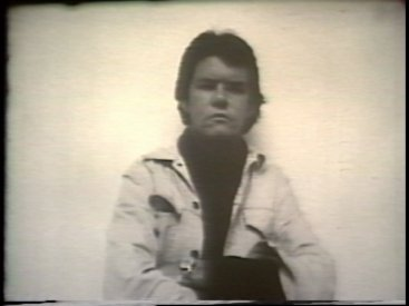 Still from Sequence 8 of Idea Demonstrations. Peter Kennedy attempts to form an after image of the camera and camera operator on his retinas.