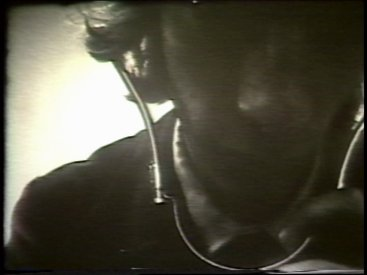 Still from Sequence 9 of Idea Demonstrations. Ian Stocks records the sound of the camera with a stethoscope.